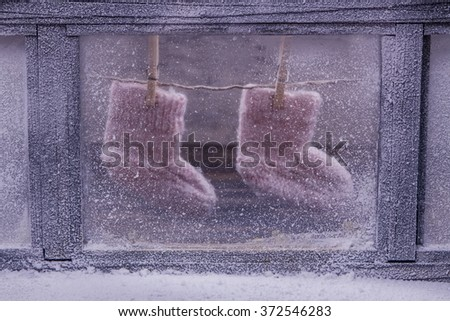 Frosted winter window. Baby knitted woolen socks - stock photo