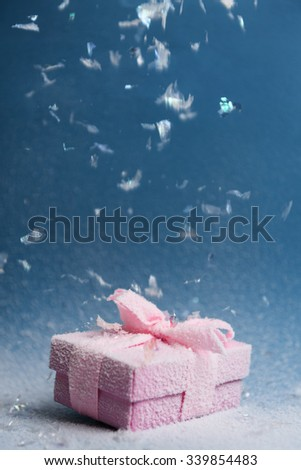 Frosty Gift under Snowfall on blue background - stock photo