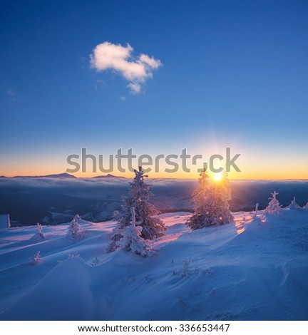 Frosty morning in mountains. Landscape with the rising sun. Snowy winter - stock photo