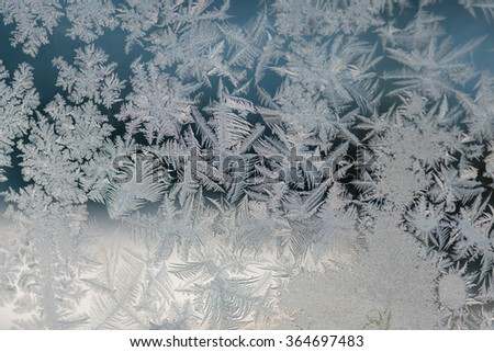 Frosty natural pattern at a winter window glass. Hoarfrost background.  - stock photo
