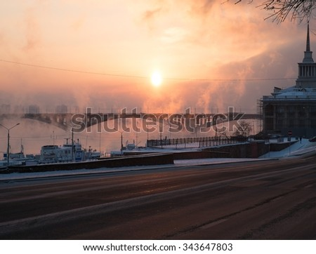 Frosty sunset with steam from the river. The City Of Krasnoyarsk, Siberia, Russia. - stock photo
