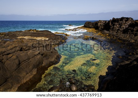 froth coastline in lanzarote spain pond  rock stone sky cloud beach  water  musk  and summer     - stock photo