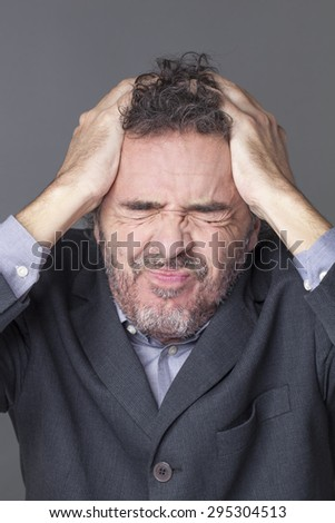 frowning corporate man holding his head with both hands for expressing dramatic mistake at work - stock photo
