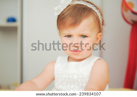 frowning girl in white dress with headband - stock photo