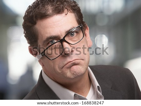 Frowning stressed businessman with funny expression - stock photo