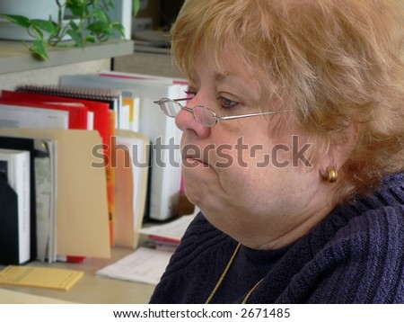 Frowning woman in office - stock photo