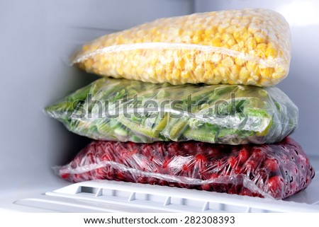 Frozen berries and vegetables in bags in freezer close up - stock photo