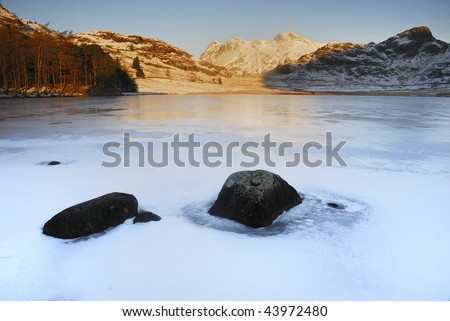 Frozen Blea Tarn and the Langdale Pikes in winter in the English Lake District - stock photo