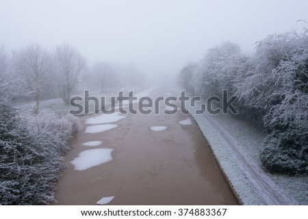 Frozen Canal covered in frost on a cold and foggy Winters day - stock photo