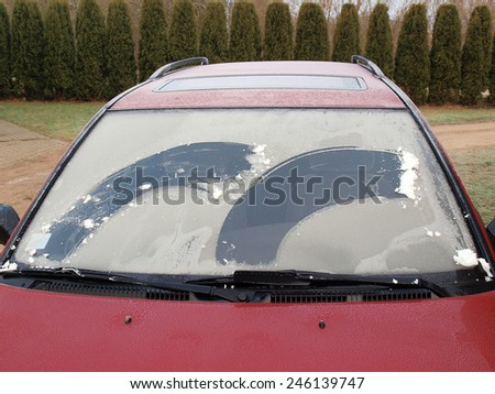 Frozen car front window partly cleaned by two brushes - stock photo