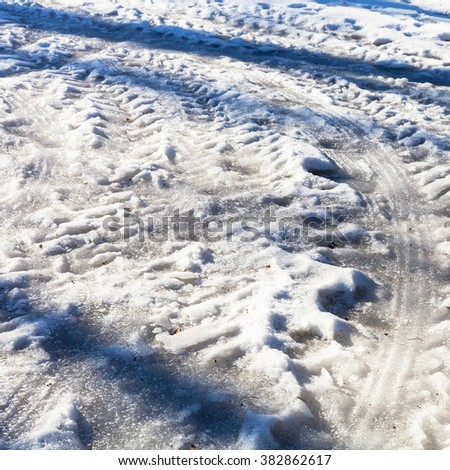 frozen car traces on snowy country road in cold winter day - stock photo