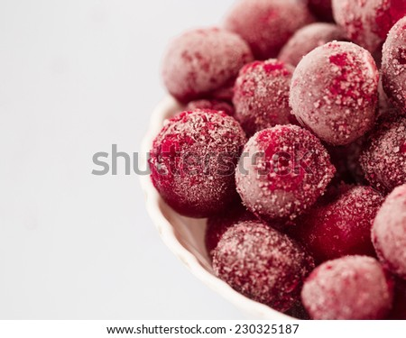 frozen cherries in the plate on gray background - stock photo