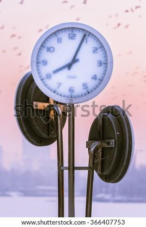 Frozen clocks covered by frost outside in winter season - stock photo