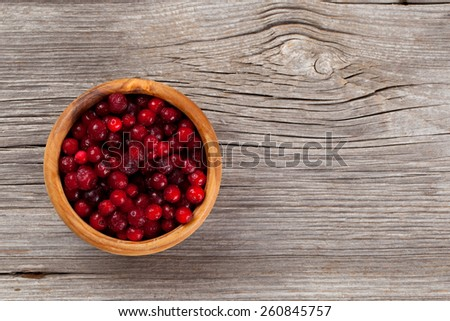 frozen cowberries on wooden background - stock photo
