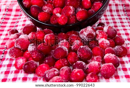 Frozen cranberries on a background of red, checkered tablecloths - stock photo