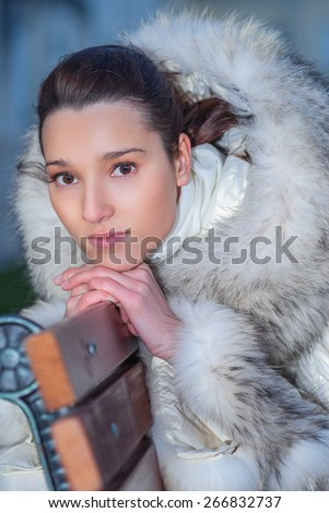Frozen girl in black raincoat sits on city bench. - stock photo