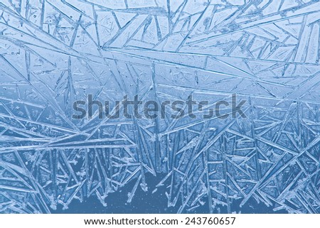 Frozen glass. Ice flowers. Frost flowers. Window frost. Winter window. Frozen window. Craquelure. (Macro. Soft focus. Toned photo). - stock photo