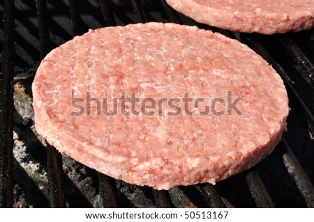 Frozen Hamburger Patties Cooking on the Grill - stock photo