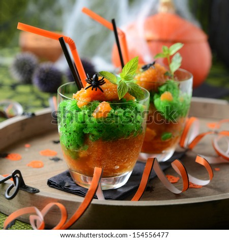 frozen kiwi and peach pieces with halloween decoration - stock photo