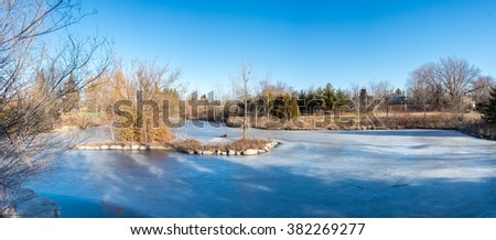 Frozen lake, in the middle of winter time, due to low temperatures the trees along side the like lack leaves and and vegetation - stock photo