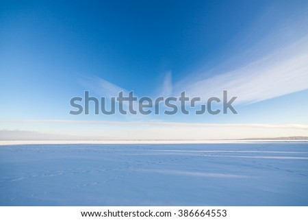 Frozen lake scape and blue sky - stock photo