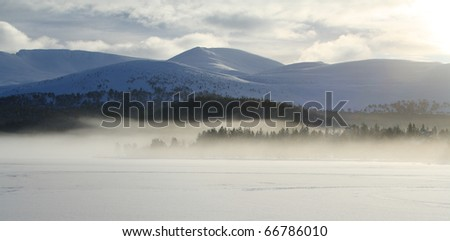 Frozen lake with mist in the distance. (Loch Morlich, Scottish Highlands. This area is in the Cairngorm National Park.) - stock photo