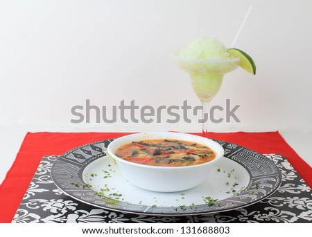Frozen lime margarita with bowl of tortilla soup in black, red and white color scheme with Mexican Aztec graphics on platter. - stock photo