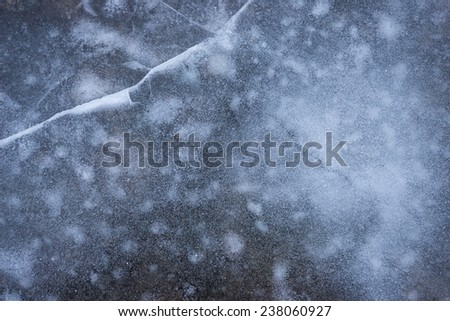 Frozen pond with fractures and bubbles trapped inside the ice. Backgrounds and textures. - stock photo