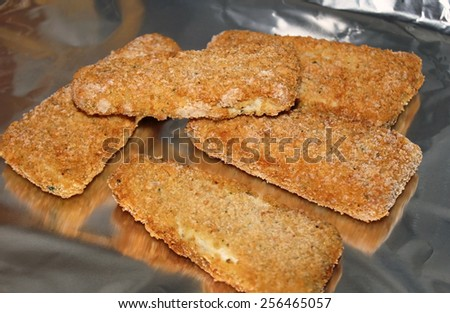 Frozen portions of battered fish on aluminum foil in oven - ready for baking - stock photo