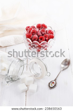 Frozen raspberries in a glass bowl and sugar over white wooden background - stock photo
