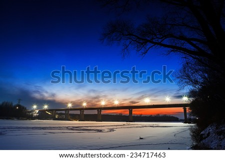 Frozen river with lighted lanterns automobile bridge. - stock photo