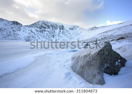 frozen rock and lake in the mountains covered in snow - stock photo