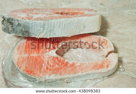 Frozen salmon raw red fish steak on the table - stock photo