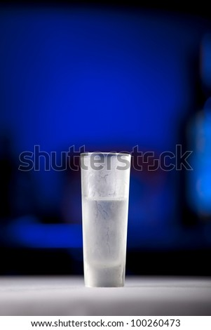 Frozen shot glass standing on a table with blue background - stock photo