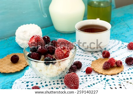frozen strawberries, raspberries and currants in a plate with cottage cheese, a cup of tea and milk jug. Healthy and wholesome breakfast - stock photo