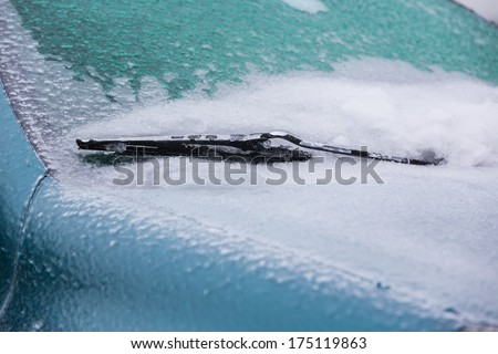 Frozen wiper of the car with icicles, ice and frost - stock photo