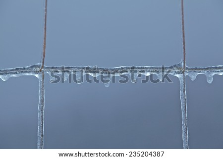 Frozen wire fence in winter frost - stock photo
