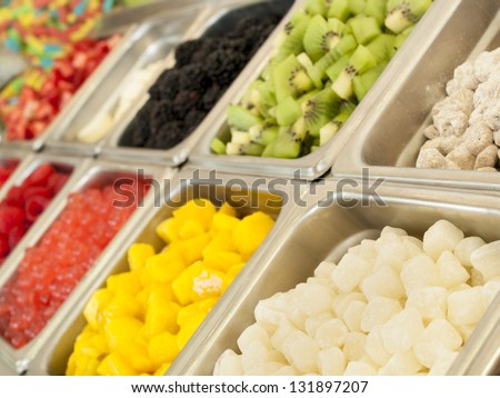 Frozen yogurt toppings bar. Yogurt toppings ranging from fresh fruits, nuts, fresh-cut candies, syrups and sprinkles. - stock photo