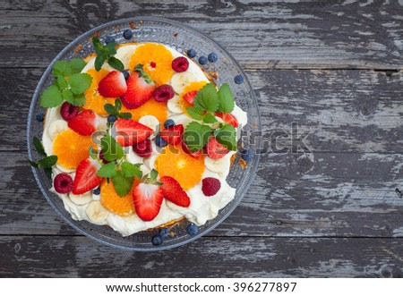 Fruit and berries cake on dark wooden table, top view, easter, spring - stock photo