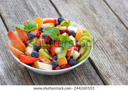 Fruit and berry salad on wooden table, horizontal, close-up - stock photo