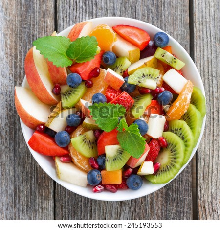 Fruit and berry salad on wooden table, top view, close-up - stock photo