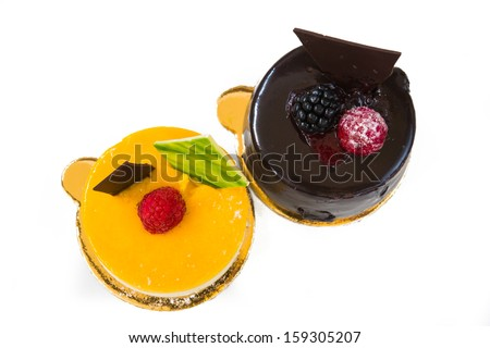 fruit and chocolate cake decorated with fruit on a white background, shot from above - stock photo