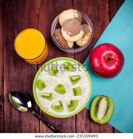 Fruit and oatmeal yogurt on the table. Apple, kiwi fruit, pastries and juice on the table as a nutritious vegetarian breakfast. Concept of healthy food. - stock photo