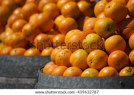 Fruit background. Heap of bright ripe oranges at the barrel - stock photo