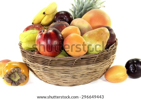 Fruit basket with various colorful fruits on a light background - stock photo