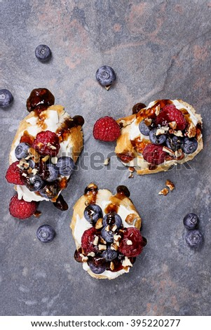 Fruit Bruschetta with cheese spread, fresh berries, walnuts and a glaze of balsamic and fruit sauce. - stock photo
