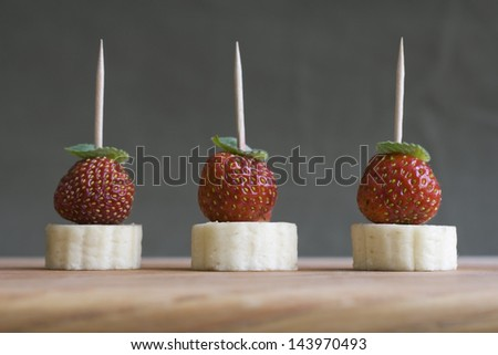 Fruit canape - banana and strawberry with mint leaf - stock photo