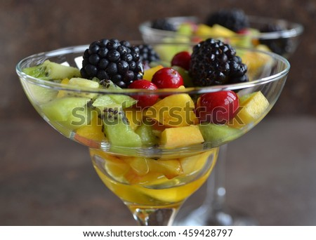 Fruit Cocktail Dessert: A Healthy Solution for Your Sweet Tooth. Fresh Organic Ingredients - Blackberry, Kiwi Fruit,Peach, Cranberry, Clear Honey. Perfect Summery Taste. - stock photo
