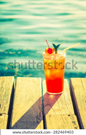 Fruit cocktail glass at pool - vintage filter effect - stock photo
