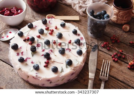 Fruit dairy multi-colored jelly on a plate. Fruit yogurt cake on wooden background. Cream and yogurt based fruit filling topped with jelly. Blueberries, blackberries, stawberries. Rustic food style. - stock photo